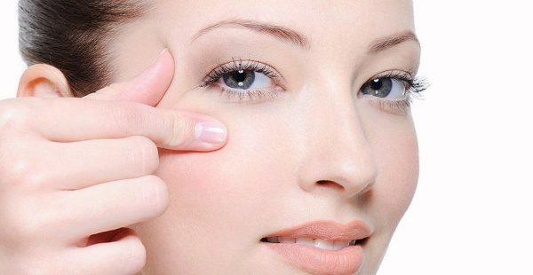 Лицо девушки и пальцы на коже вокруг глаз