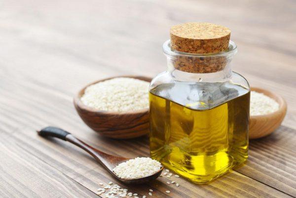 Семена кунжута на столе и масло в стеклянной бутылочке