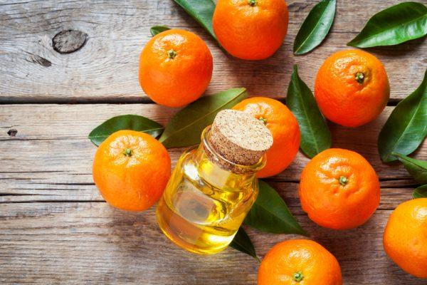 Масло мандарина в прозрачном флаконе и фрукты