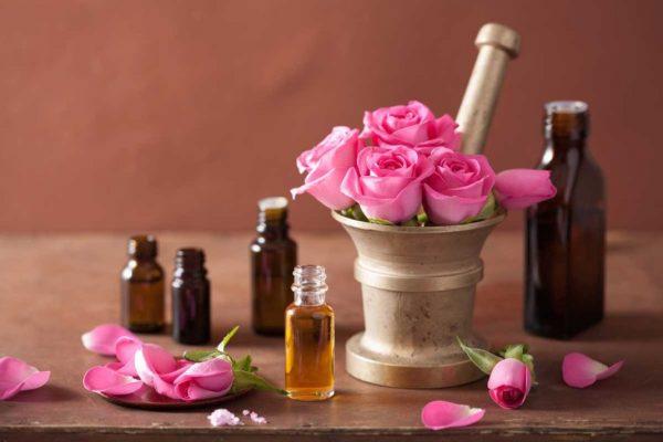 Масло розы в прозрачной бутылочке и розовые цветы