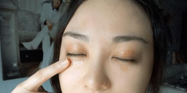Девушка наносит масло под глаза