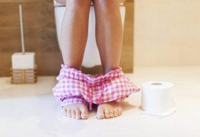 Ноги девушки, сидящей на унитазе