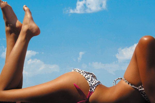 Ноги и плечи загорелой девушки на фоне голубого неба