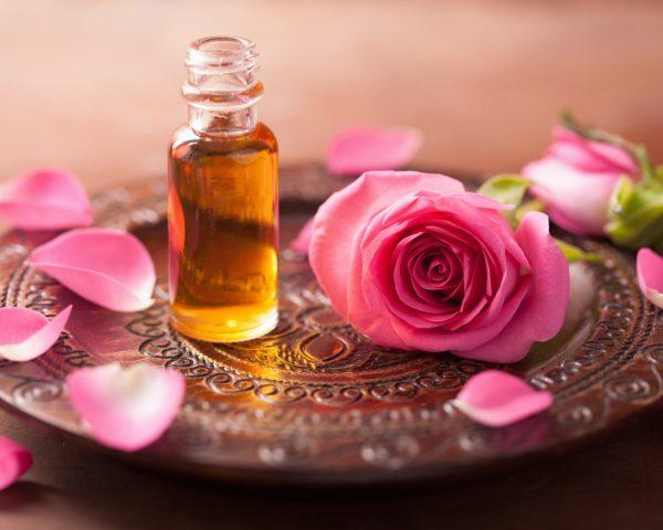 Роза и флакончик масла на подносе