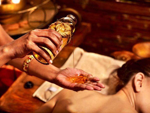 Рука массажиста, наливающего в ладонь масло на фоне лежащей девушки