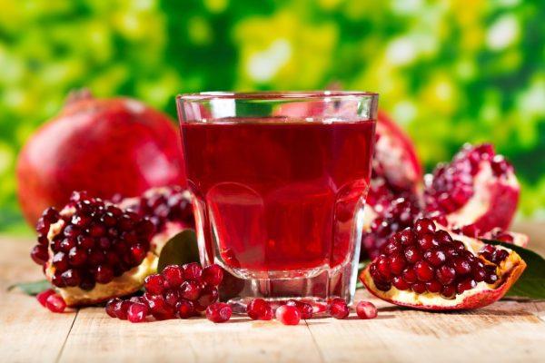 Сок граната в прозрачном бокале и плоды