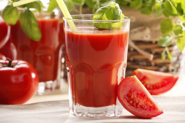 Томатный сок в прозрачном стакане и овощи