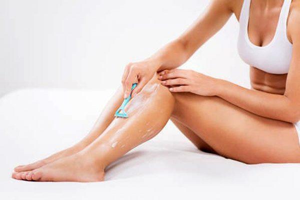 Женщина бреет ноги