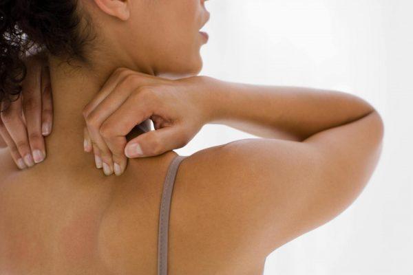 Женщина массирует себе шею