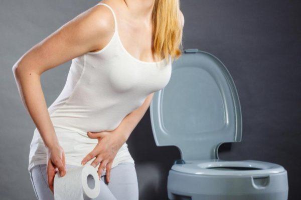 Женщина с рулоном туалетной бумаги держится за низ живота
