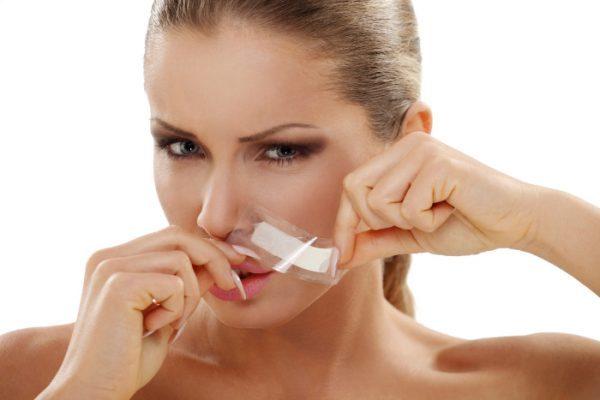 Депиляция волосков над верхней губой при помощи восковой полоски
