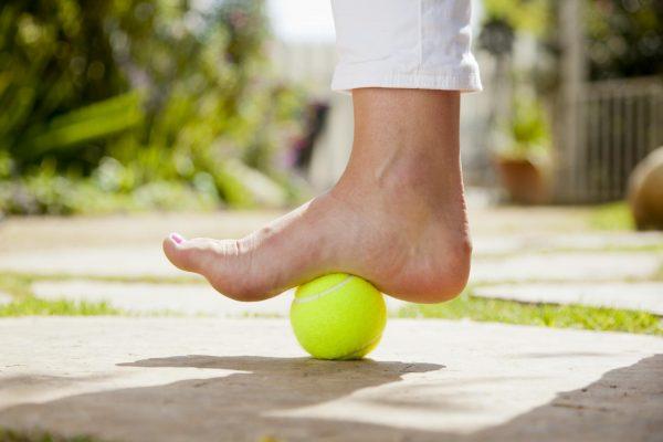 Нога стоит на теннисном мяче