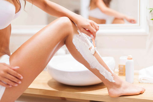 Девушка бреет ногу