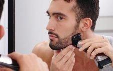 Мужчина бреется электробритвой