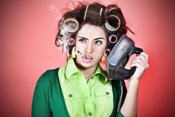 Женщина в бигуди гладит волосы утюгом