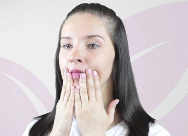 Девушка держит уголки губ ладонями