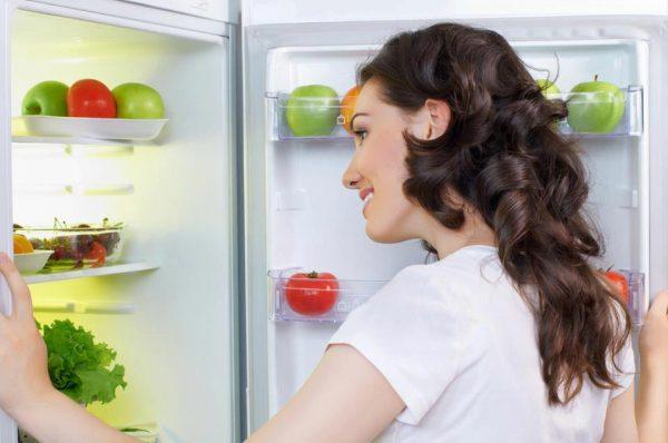 Девушка открывает холодильник