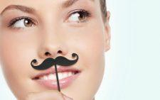 Девушка прикладывает к лицу искусственные усы