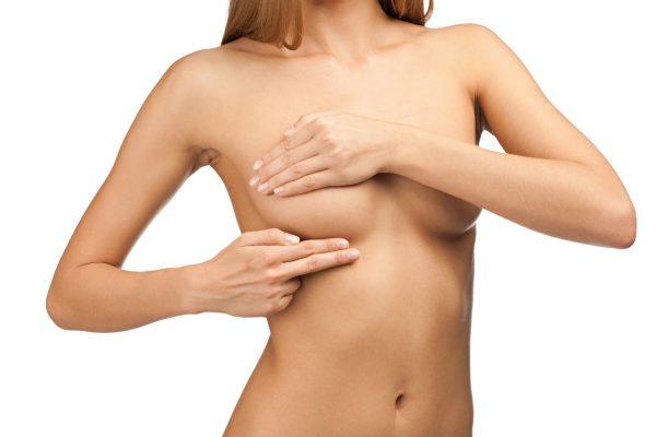 Девушка прикрывает руками грудь
