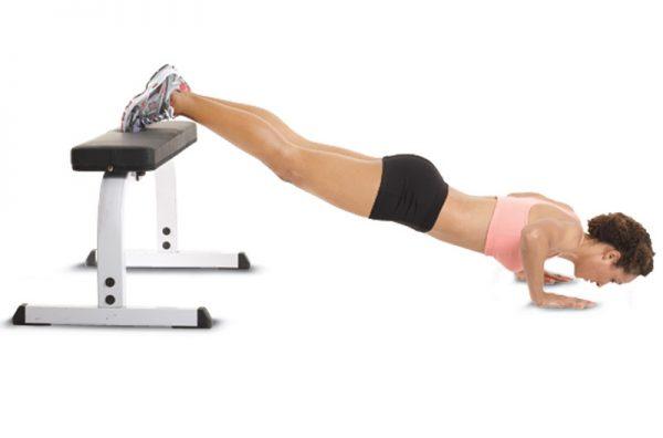 Девушка отжимается, используя горизонтальную опору для ног