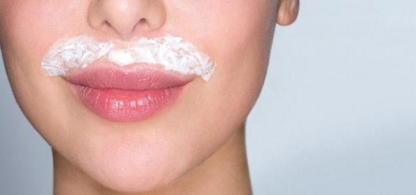 Лицо девушки с кремом-депилятором над верхней губой