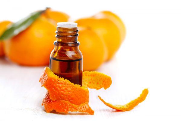 Флакон с мандариновым маслом обвит мандариновой коркой, на заднем фоне мандарины
