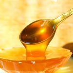 Мёд стекает с ложки в стеклянную вазочку