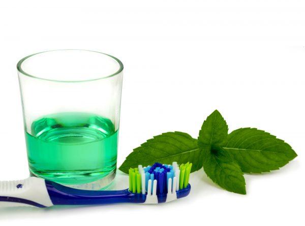 Стакан с мятной жидкостью, листики мяты и зубная щётка