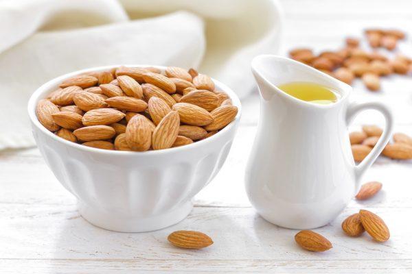 Миндальные орехи и масло в кувшине