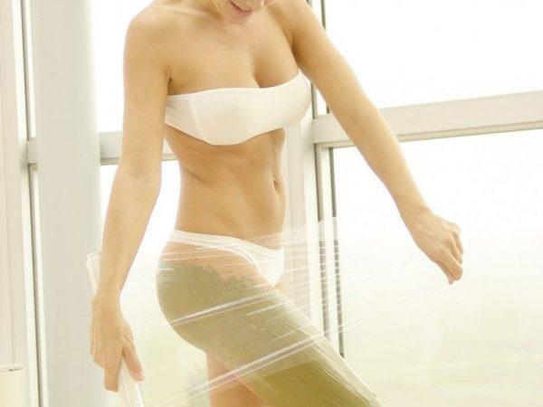 Девушка оборачивает тело пищевой плёнкой