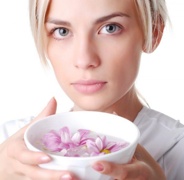 Девушка держит миску с водой и цветами