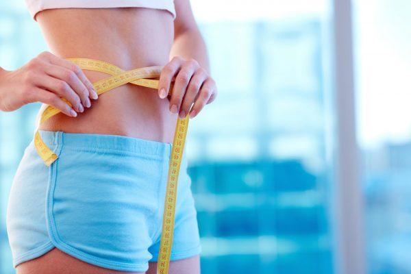 Девушка в шортах измеряет объём талии сантиметровой лентой