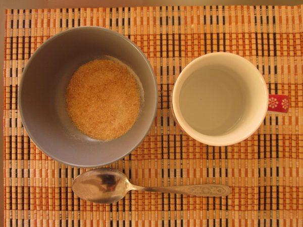 Желатин в миске, стакан с водой и чайная ложка