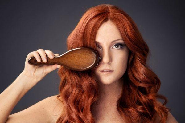 Рыжая девушка расчёсывает волосы