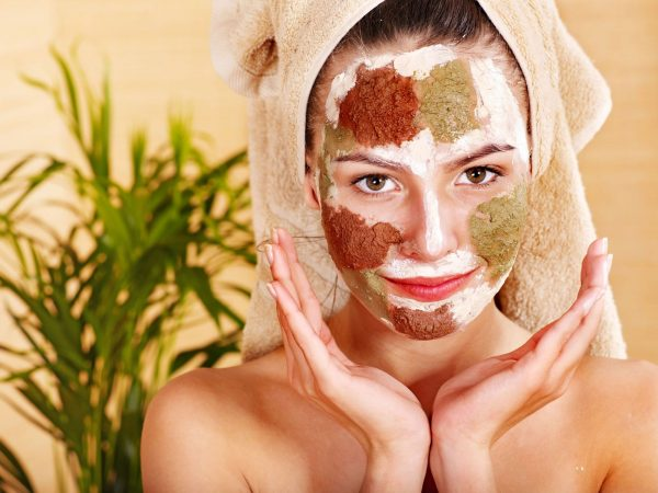 Лицо девушки с косметической маской из нескольких составов разного цвета
