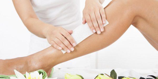 Женские руки, накладывающие на ногу восковую полоску
