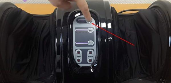 Нажатие кнопки включения на приборной панели массажёра