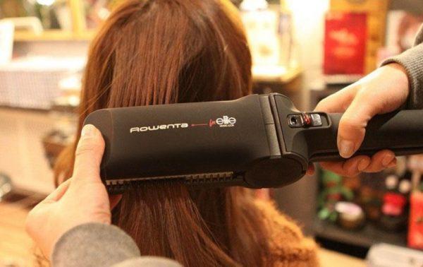 Девушке выпрямляют волосы утюжком