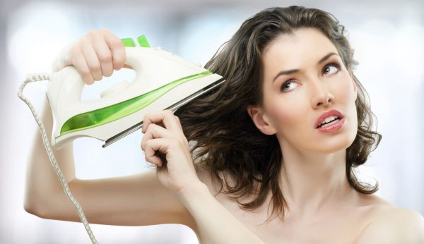 Женщина гладит волосы утюгом