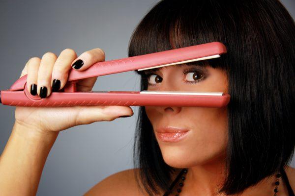 Девушка и утюжок для выпрямления волос
