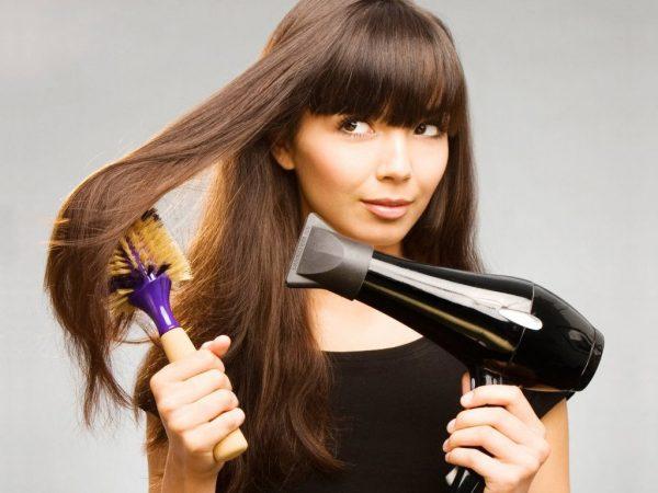 Девушка сушит волосы феном и расчёсывает их