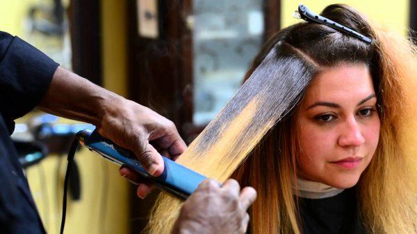 Рука парикмахера и девушка с прядью вытянутых утюжком волос