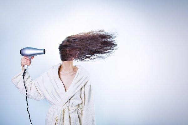 Сильная струя воздуха из фена направлена на волосы