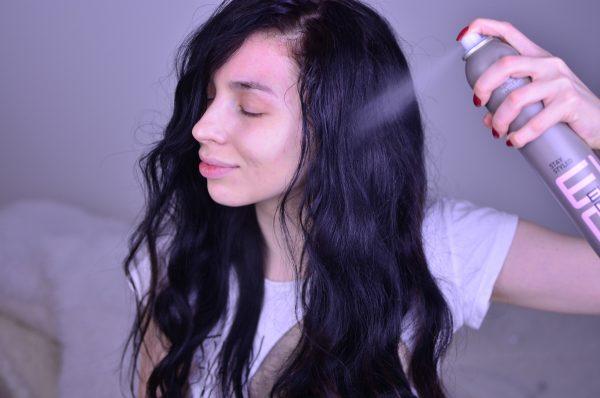 Девушка распыляет лак на волосы