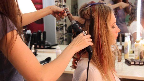 Женщине завивают волосы коническим стайлером