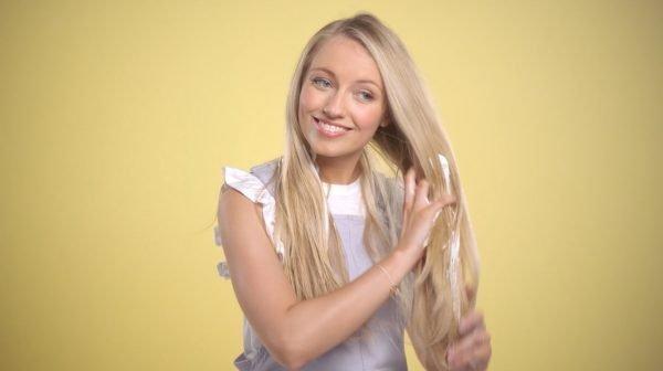 Девушка наносит мусс на волосы
