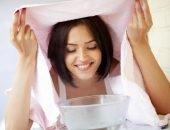 Брюнетка с розовым махровым полотенцем над головой склонилась к чаше с водой