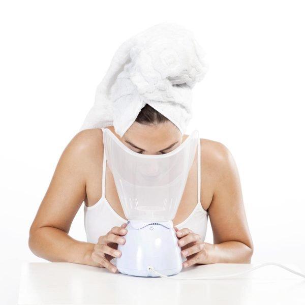 Женщина с белым полотенцем на голове распаривает лицо в чаше парового ингалятора