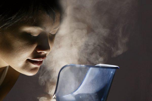Женское лицо в темноте над парами из чаши ингалятора