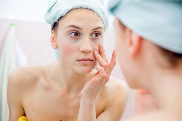 Женщина в тюрбане из полотенца перед зеркалом трогает кожу лица